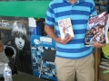 Author Maurey Dean displays a first edition of his Rock Revolution (1966) and his new reissue Rock Revolution Rolls On.
